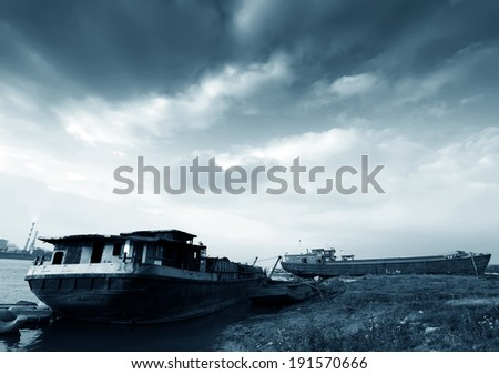 Under dramatic clouds, on the river's flood, two abandoned barge.