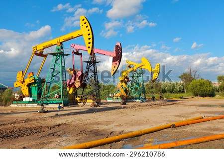 Under sunny golden yellow and pink Oil pump oil rig energy industrial machine for petroleum crude of countryside dirt road - stock photo