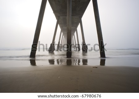Under the Hermosa Beach Pier During a Foggy Sunset - stock photo