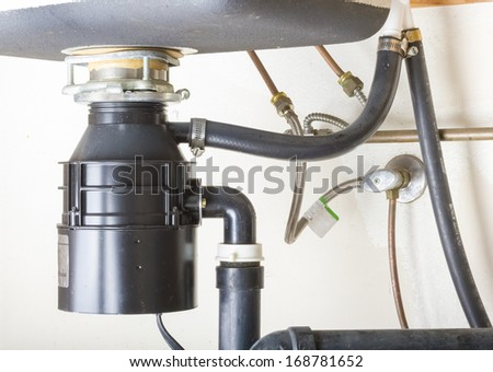 Under the sink garbage disposal unit.