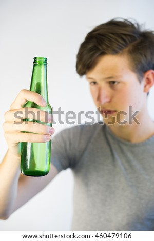 Underage drinker looking at a beer bottle worringly.