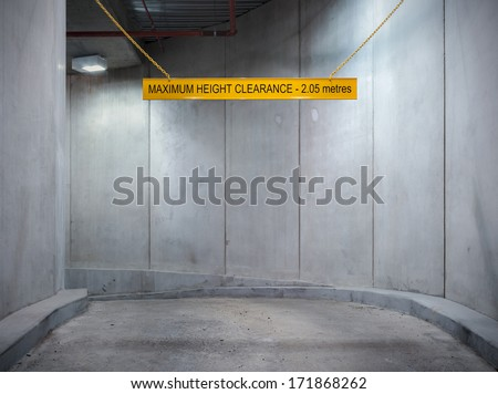Underground parking garage concrete entrance ramp with height limit sign. - stock photo