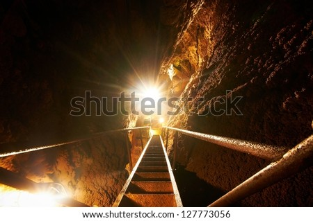 Underground staircase a cave in bright light - stock photo