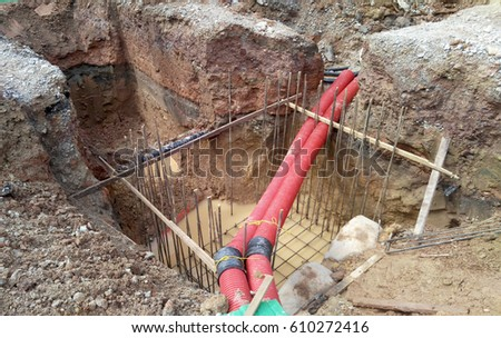 Underground utility and services corrugated pipe lay by workers at the construction site.