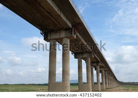Underside of an elevated roads. Transport interchange under the sky background. High overpass on the sky background - stock photo