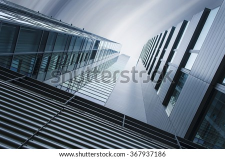 underside panoramic and perspective view to steel blue glass high rise building skyscrapers, industrial architecture - stock photo