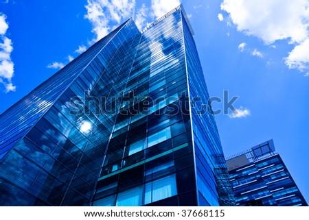 Underside view to corner of black glass building - stock photo