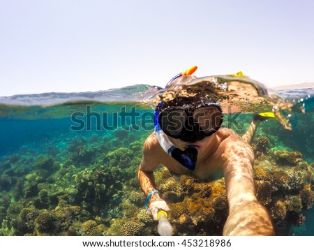 Underwater and surface split view in the tropics paradise with snorkeling man, fish and coral reef, under and above waterline, beautiful view on tropical sea.  - stock photo