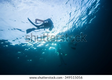 Underwater Blue Sea and diver on the sea surface  - stock photo