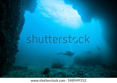 Underwater blue sea and scuba divers. - stock photo
