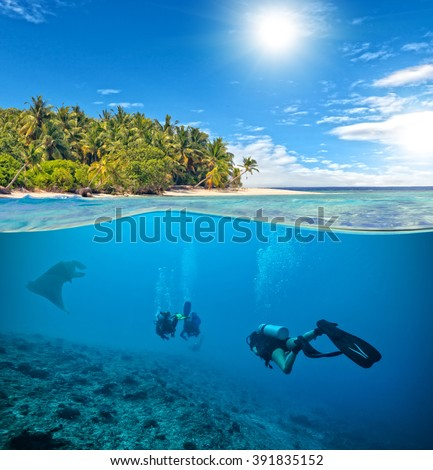 Underwater coral reef with scuba divers and manta - stock photo