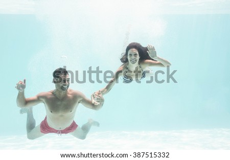 Underwater couple holding hands and enjoying in swimming pool - stock photo