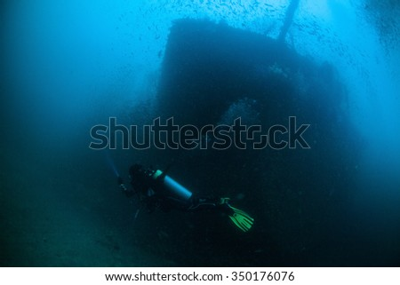 Underwater deep blue sea and scuba diver explore wreck ship  - stock photo