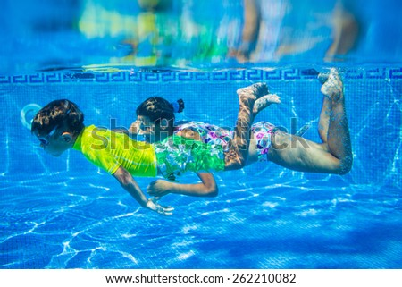 Underwater happy cute girl and boy in swimming pool - stock photo