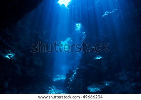 underwater landscape. cave in the coral reef lit sun rays. - stock photo