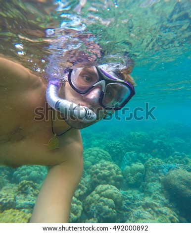 Underwater landscape with man. Snorkel in undersea gear making selfie with coral reef. Oceanic ecosystem and human image. Diving person in glass goggles and pipe. Clean turquoise water of tropical sea