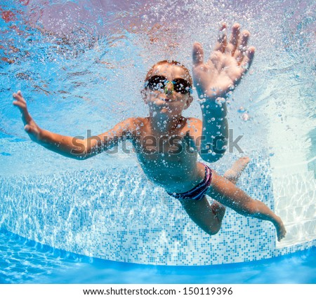 Underwater little kid in swimming pool with goggles.