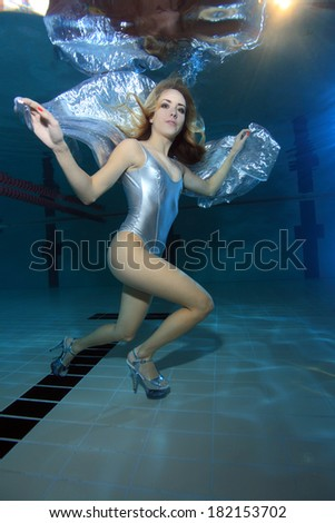 Underwater model with silver swimsuit and high heels underwater in the pool