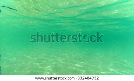 Underwater on a shallow sandy seabed with sunlight through water surface, natural scene - stock photo