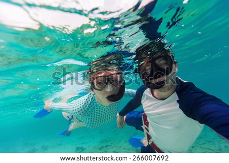 Underwater photo of a young couple snorkeling at tropical ocean