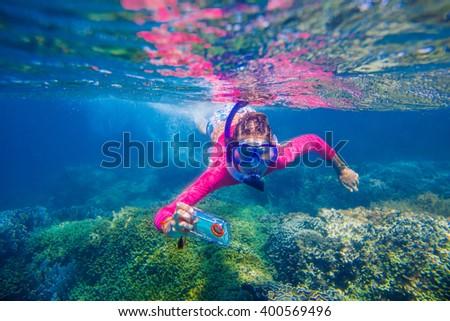 Underwater photo of girl with camera - stock photo