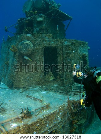 Underwater Photographer shooting the Radar Tower on a Sunken Destroyer - stock photo