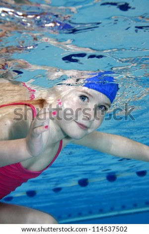 Underwater picture of a young girl in the swimming-pool.