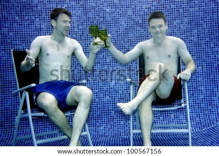 Underwater picture two young man sitting on chairs and making a toast.