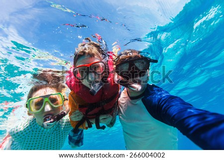 Underwater portrait of family snorkeling together at clear tropical ocean - stock photo