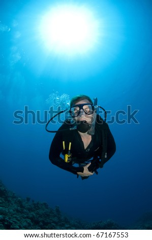 underwater scuba diver with sun ball behind - stock photo