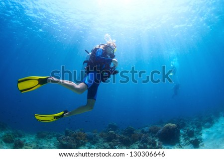 Underwater shoot of a divers swimming in a blue clear water - stock photo