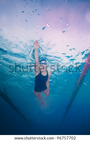 Underwater shoot of a professional woman swimming in crawl style - stock photo