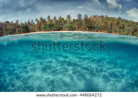 Underwater shoot of a sandy sea bottom and green tropical island above sea surface - stock photo