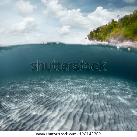 Underwater shoot of a sandy sea bottom and green tropical island with cloudy sky above sea surface - stock photo