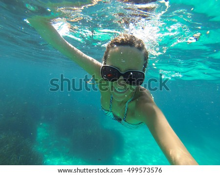Underwater shoot of a woman swimming over sandy sea bottom