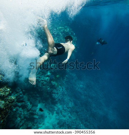 Underwater shoot of a young man jumping in a red sea - stock photo