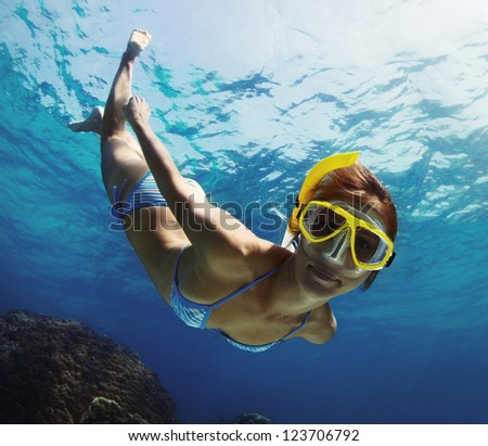 Underwater shoot of a young smiling lady snorkeling and doing skin diving in a tropical sea - stock photo