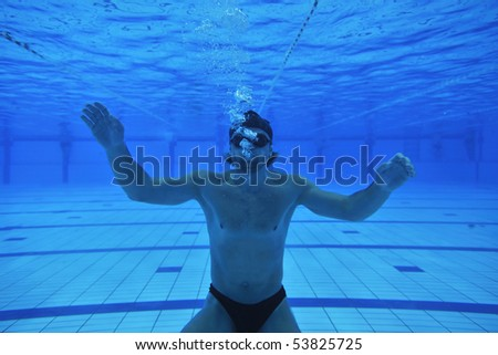 underwater shoot of swimming pool with good looking young swimmer - stock photo