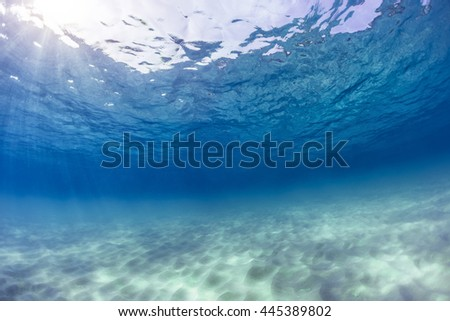 Underwater shot of an infinite sandy sea bottom with clear blue water and waves on its surface - stock photo