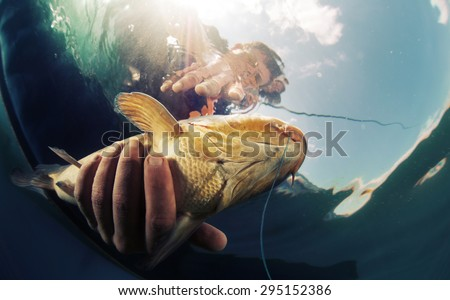 Underwater shot of the fisherman holding the fish - stock photo