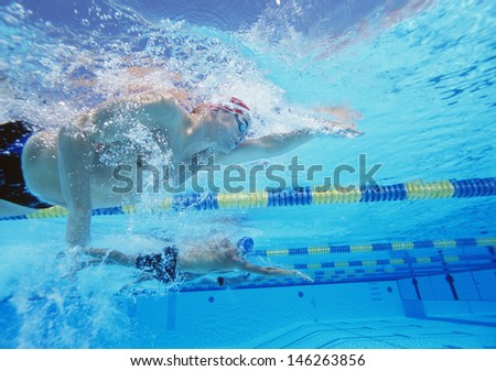 Underwater shot of three male athletes in swimming competition - stock photo