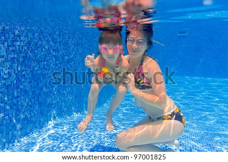 Underwater smiling family having fun and playing in swimming pool. Happy mother and kid swim underwater. Summer vacation. - stock photo