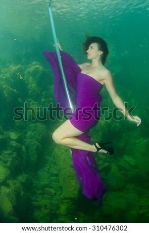 Underwater striptease beautiful slim girl - stock photo