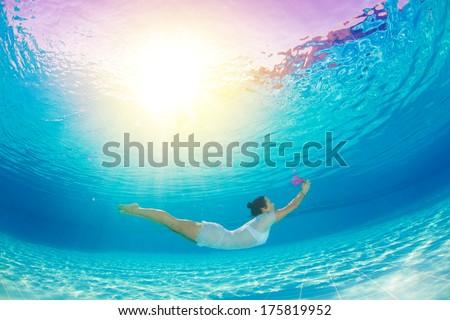 underwater swimming with flowers - stock photo