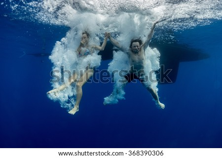 Underwater view of the young couple having fun and jumping into the clear sea from a boat - stock photo