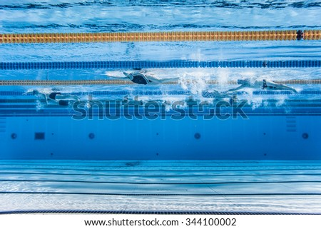 underwater view of unrecognizable professional swimmers training into a 50m outdoor olympic pool