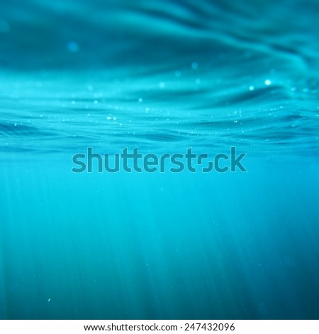 Underwater view with sun beams in turquoise water - stock photo