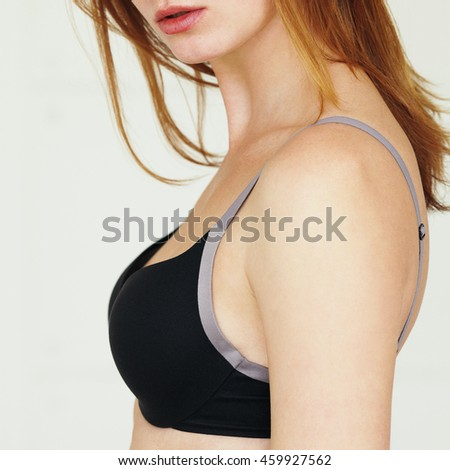 Underwear concept. Young sexy woman with red hair in lingerie posing on white background. Natural beauty. Close up - stock photo