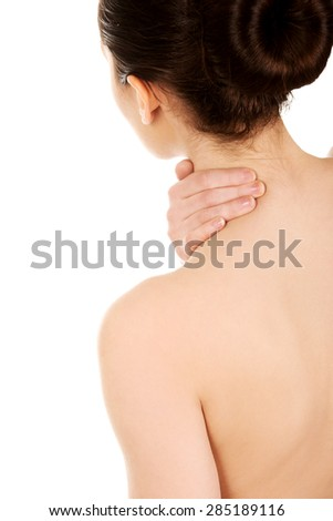 Undressed woman with neck pain from behind.