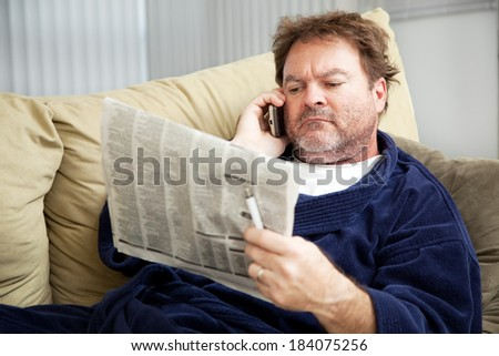 Unemployed man at home on the couch looking at the classified ads in the newspaper.   - stock photo